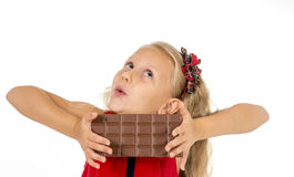 Little beautiful female child in red dress holding happy delicious chocolate bar  Royalty Free Stock Photos