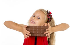 Little beautiful female child in red dress holding happy delicious chocolate bar in her hands eating delighted. In children sugar and sweet addiction isolated royalty free stock images