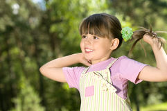 Little beautiful girl. The small beautiful girl is dared, holds a hand for hair, on the nature, in a sunny day. Profile Adobe RGB (1998 Royalty Free Stock Image