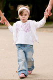 Little beautiful girl. Daughter holds the hands of the father and mother Royalty Free Stock Images