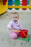 Little beautiful girl with a baby barrette color play in the playground sandbox sand pail, shovel and rake Stock Photo