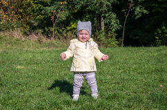 Little beautiful girl baby coat, hat and jeans playing in the park walking on green grass doing their first steps smiling and enjo Royalty Free Stock Photos
