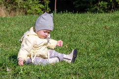 Little beautiful girl baby coat, hat and jeans playing in the park walking on green grass doing their first steps smiling and enjo Stock Photo