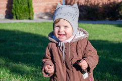 Little beautiful girl baby coat, hat and jeans playing in the park walking on green grass doing their first steps smiling and enjo Stock Photography