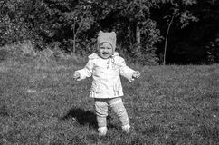 Little beautiful girl baby coat, hat and jeans playing in the park walking on green grass doing their first steps smiling and enjo Royalty Free Stock Photography