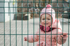 Little beautiful girl baby crying with tears in his eyes and a sad, sad emotions shut down as a punishment for a fence of metal la Royalty Free Stock Photography