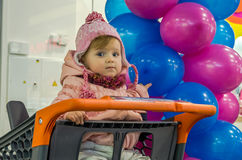 Little beautiful girl in a baby jacket, pants and hat sitting in a plastic basket of products from the supermarket in the shopping stock photos