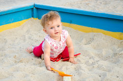 Little beautiful girl baby play in the sandbox and sand toys on the playground Stock Images
