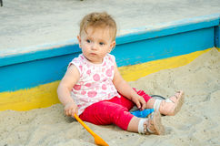 Little beautiful girl baby play in the sandbox and sand toys on the playground Stock Photos
