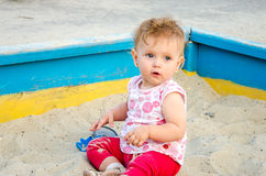 Little beautiful girl baby play in the sandbox and sand toys on the playground Stock Image