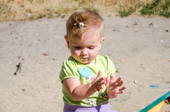 Little beautiful girl baby playing in a sandbox on the playground Royalty Free Stock Photo