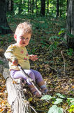 Little beautiful girl baby playing with a stick sitting on a log Royalty Free Stock Photos
