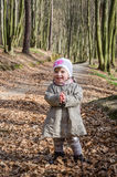 Little beautiful girl in a baby raincoat, hat and scarf is played in spring forest dry leaf litter throwing their smiles in a good Stock Photo