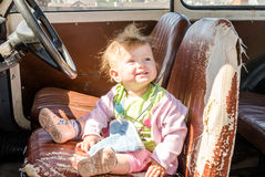 Little beautiful girl baby sitting on an old leaky leather seat behind the wheel of a vintage retro car Royalty Free Stock Photography