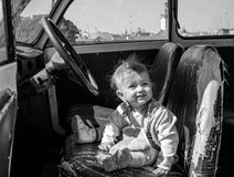 Little beautiful girl baby sitting on an old leaky leather seat behind the wheel of a vintage retro car  black and white image Stock Photos