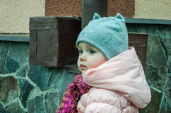 Little beautiful girl baby walking outdoors in jacket and hat Royalty Free Stock Photography