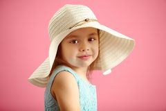 558a019bae3 Little beautiful girl in beach hat and blue dress on pink isolated  background. Cute child