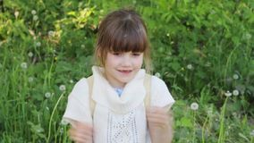 Little beautiful girl blows two white dandelion outdoor in summer day stock footage