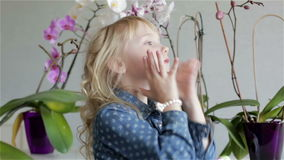 A little beautiful girl in a blue dress is correcting her blonde curly hair. stock video footage