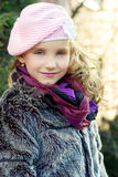 Little beautiful girl with blue eyes in pink hat standing on the street Royalty Free Stock Photos