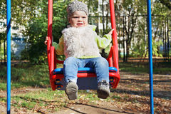 Little beautiful girl in blue jeans swings Royalty Free Stock Photo