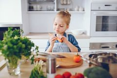 Little girl in a kitchen. A little and beautiful girl in a blue shirt and apron is preparing a fresh vegetable salad at home in the kitchen royalty free stock images