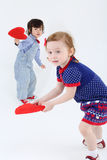 Little beautiful girl and boy stand and hold red hearts Stock Photo