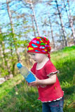 Little beautiful girl in bright clothes holding a bottle in hand Royalty Free Stock Photography