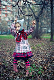Little beautiful girl. In a checkered coat and a felt hat on nature stock illustration