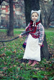 Little beautiful girl. In a checkered coat and a felt hat on nature royalty free illustration