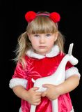 Little beautiful girl in Christmas Santa costume, with fur balls on her head, holding a deer in ruach. The concept of celebrating royalty free stock images