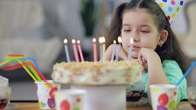 A little girl looks at a cake with candles and sad stock video footage