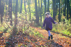Little beautiful girl in coat runs in park Royalty Free Stock Image