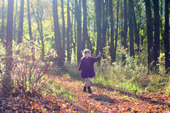 Little beautiful girl in coat runs in park Royalty Free Stock Images