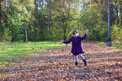 Little beautiful girl in coat throws up leaves Royalty Free Stock Photo