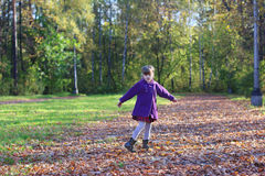 Little beautiful girl in coat whirls among dry leaves Royalty Free Stock Image