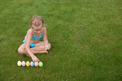 Little beautiful girl considers Easter eggs on Stock Images