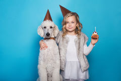 Little beautiful girl with dog celebrate birthday. Friendship. Love. Cake with candle. Studio portrait over blue background Royalty Free Stock Image