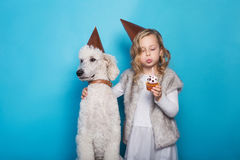 Little beautiful girl with dog celebrate birthday. Friendship. Love. Cake with candle. Studio portrait over blue background Stock Image
