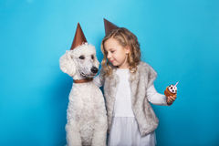 Little beautiful girl with dog celebrate birthday. Friendship. Love. Cake with candle. Studio portrait over blue background. Little beautiful girl with dog stock photography