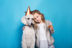 Little beautiful girl with dog celebrate birthday. Friendship. Love. Cake with candle. Studio portrait over blue background. Little beautiful girl with dog Royalty Free Stock Photo