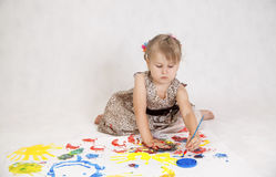 Little beautiful girl draws paints, hands in the paint Royalty Free Stock Images