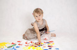 Little beautiful girl draws paints, hands in the paint Royalty Free Stock Image