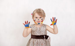 Little beautiful girl draws paints, hands in the paint. Beautiful smart girl draws paints smiling, hands in the paint stock photo