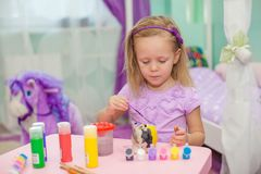 Little beautiful girl draws paints on the table Stock Photo