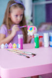 Little beautiful girl draws paints on the table Stock Photography
