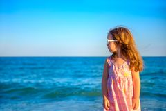 Little beautiful girl in a dress standing on the beach. Looking away and dreaming of something Stock Photos