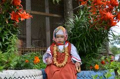 a little beautiful girl dressed in a folk caftan with bagels on her neck sits near the flowers royalty free stock photos