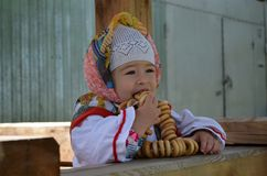 little beautiful girl dressed in folk caftan eating bagels near the well royalty free stock photography