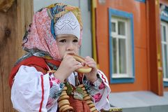 beautiful girl dressed in folk caftan eating bagels near the well royalty free stock photos